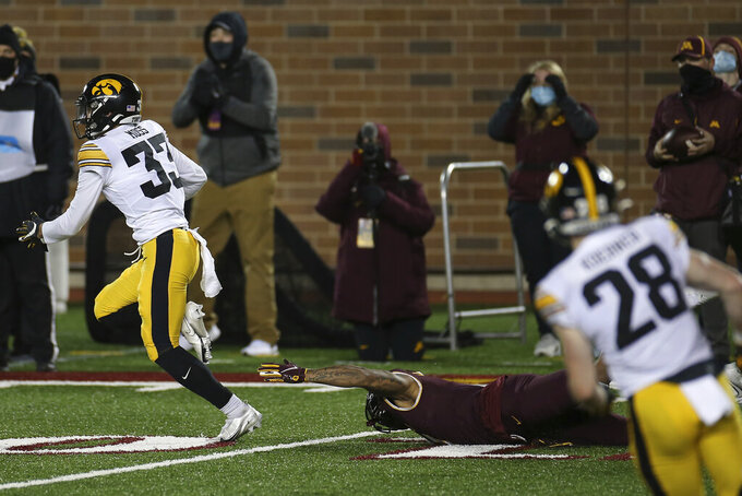 Iowa defensive back Riley Moss (33) outruns Minnesota wide receiver Chris Autman-Bell (7) after intercepting a pass during the second half of an NCAA college football game Friday, Nov. 13, 2020, in Minneapolis. Iowa won 35-7. (AP Photo/Stacy Bengs)