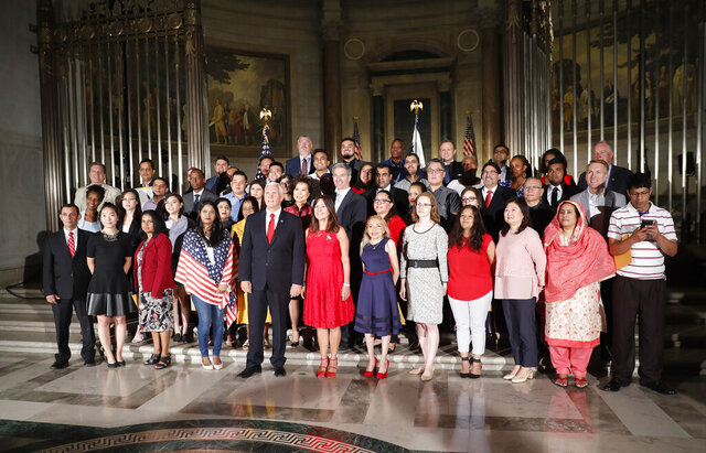 FILE - In a Thursday, July 4, 2019 file photo, Vice President Mike Pence, center, his wife Karen Pence, pose for a group photo with new naturalized citizens following a naturalization ceremony at the National Archives in Washington. Almost half of the foreign-born who moved to the U.S. in the past decade were college-educated, a level of education greatly exceeding immigrants from previous decades, as the arrival of highly skilled workers supplanted workers in fields like construction that shrunk after the Great Recession. New figures released this week by the U.S. Census Bureau show that 47% of the foreign-born population who arrived in the U.S. from 2010 to 2019 had a bachelor's degree or higher, compared to 36% of native-born Americans and 31% of the foreign-born population who entered the country in or before 2009. (AP Photo/Pablo Martinez Monsivais, File)