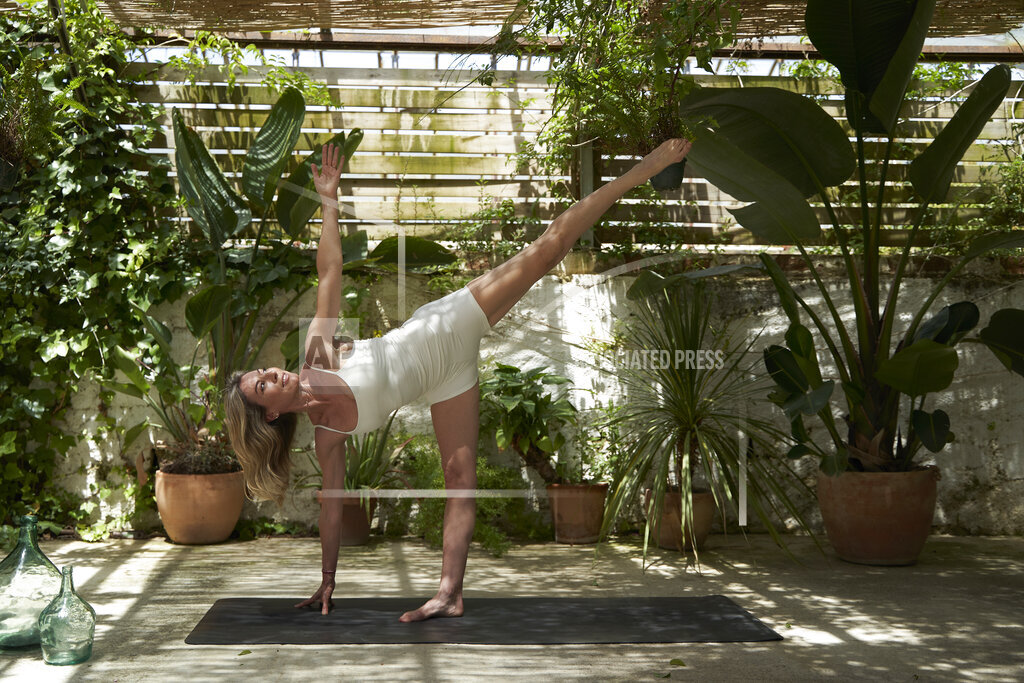 Woman doing stretching and balancing exercise on mat in backyard