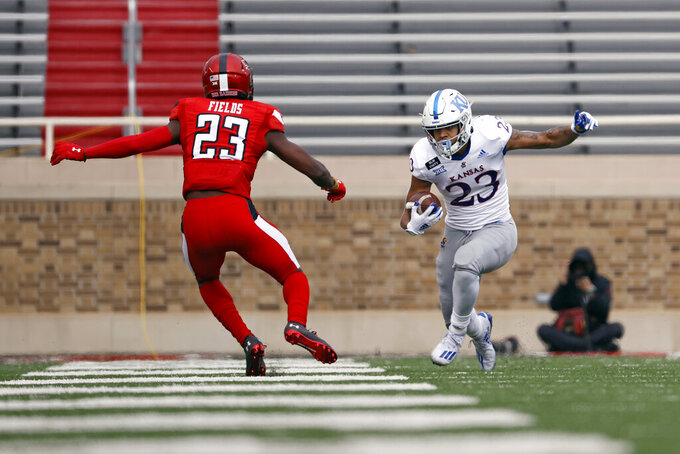 Kansas' Amauri Pesek-Hickson (23) tries to break away from Texas Tech's DaMarcus Fields (23) during the first half of an NCAA college football game Saturday, Dec. 5, 2020, in Lubbock, Texas. (AP Photo/Brad Tollefson)