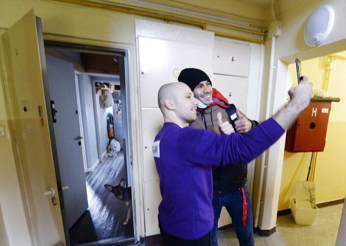 A man takes a selfie with Venezuela's 2012 Olympic champion in fencing, Ruben Limardo Gascon, who has just delivered the food he had ordered through Uber Eats in Lodz, Poland, Saturday, Nov. 14, 2020.  In Poland, where he has lived for years, Gascon delivers food for Uber Eats to support his family as he trains for the Olympics in Tokyo next summer(AP Photo/Czarek Sokolowski)
