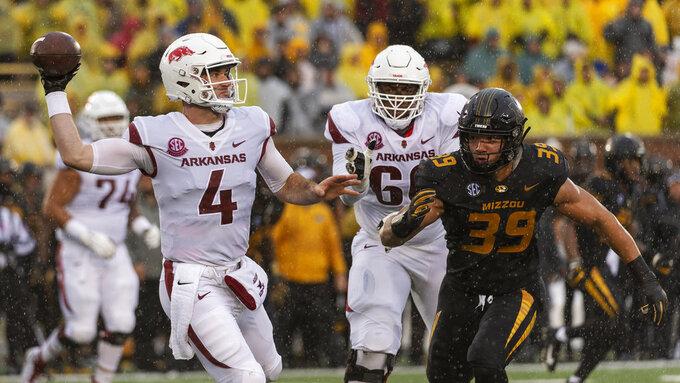 Arkansas quarterback Ty Storey, left, throws a pass before he is hit by Missouri's Chris Turner, right, during the first half of an NCAA college football game Friday, Nov. 23, 2018, in Columbia, Mo. (AP Photo/L.G. Patterson)