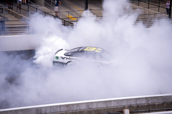 AJ Allmendinger (16) does a burn out after winning a NASCAR Cup Series auto race at Indianapolis Motor Speedway, Sunday, Aug. 15, 2021, in Indianapolis. (AP Photo/Doug McSchooler)