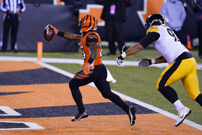 Cincinnati Bengals' Giovani Bernard (25) runs past Pittsburgh Steelers' Cameron Heyward (97) for a touchdown reception during the first half of an NFL football game, Monday, Dec. 21, 2020, in Cincinnati. (AP Photo/Michael Conroy)