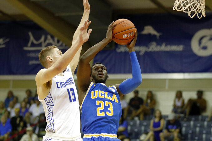 Chaminade guard Tyler Cartaino (13) tries to block UCLA guard Prince Ali (23) during the first half of an NCAA college basketball game Tuesday, Nov. 26, 2019, in Lahaina, Hawaii. (AP Photo/Marco Garcia)