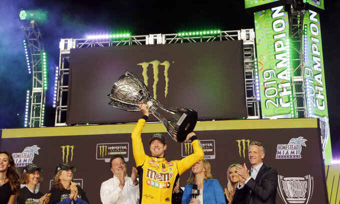 FILE - In this Nov. 17, 2019, file photo, Kyle Busch, center, holds up his trophy in Victory Lane after winning a NASCAR Cup Series auto racing season championship at Homestead-Miami Speedway in Homestead, Fla. NASCAR's season officially opens Sunday, Feb. 16, 2020, with the Daytona 500 at Daytona International Speedway. (AP Photo/Terry Renna, File)