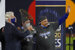 Los Angeles Dodgers manage Dave Roberts celebrates with the trophy after defeating the Tampa Bay Rays 3-1 to win the baseball World Series in Game 6 Tuesday, Oct. 27, 2020, in Arlington, Texas. (AP Photo/Tony Gutierrez)