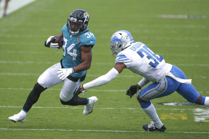 Jacksonville Jaguars running back Chris Thompson (34) tries to get around Detroit Lions cornerback Jeff Okudah, right, on a run-ing play during the second half of an NFL football game, Sunday, Oct. 18, 2020, in Jacksonville, Fla. (AP Photo/Stephen B. Morton)