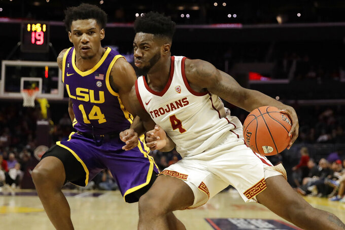 Southern California's Daniel Utomi (4) dribbles next to LSU's Marlon Taylor (14) during the first half of an NCAA college basketball game Saturday, Dec. 21, 2019, in Los Angeles. (AP Photo/Marcio Jose Sanchez)