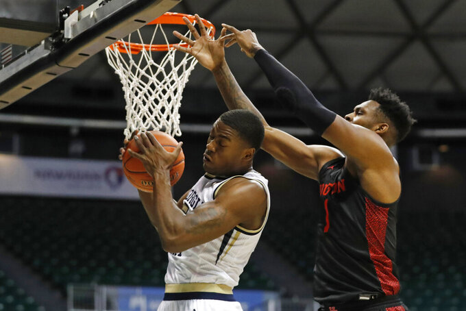 Georgia Tech forward Moses Wright (5) grabs a rebound away from Houston center Chris Harris Jr. (1) during the first half of an NCAA college basketball game Monday, Dec. 23, 2019, in Honolulu. (AP Photo/Marco Garcia)