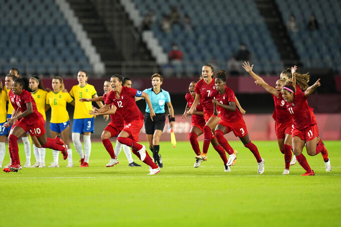 Canada players celebrate winning 4-3 in a penalty shootout against Brazil during a women's quarterfinal soccer match at the 2020 Summer Olympics, Friday, July 30, 2021, in Rifu, Japan. (AP Photo/Andre Penner)