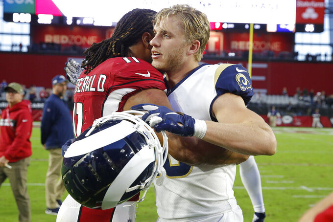 Los Angeles Rams wide receiver Cooper Kupp, right, greets Arizona Cardinals wide receiver Larry Fitzgerald after an NFL football game, Sunday, Dec. 1, 2019, in Glendale, Ariz. The Rams won 34-7. (AP Photo/Rick Scuteri)