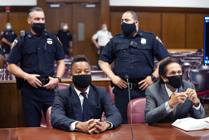 """FILE - In this Aug. 13, 2020 file photo, Cuba Gooding Jr., front left, sits at the defense table with his lawyer Marc Heller, during a hearing in his sexual misconduct case in New York. U.S. District Judge Paul Crotty issued a default judgment against Gooding on Thursday, July 29, 2021, saying it appeared the Oscar-winning """"Jerry Maguire"""" star was willfully ignoring the lawsuit and that waiting for him any longer would be unfair to his accuser. Crotty said that under the law, the 53-year-old Gooding's failure to respond and defend himself in the lawsuit constituted an admission of liability. (Steven Hirsch/New York Post via AP, Pool, File)"""