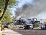 Firefighters respond to the scene of a train derailment in Tempe, Ariz.,Wednesday, July 29, 2020.  Officials say a freight train traveling on a bridge that spans a lake in the Phoenix suburb derailed and set the bridge ablaze and partially collapsing the structure.  There were no immediate reports of any leaks.  (AP Photo/Ross D. Franklin)