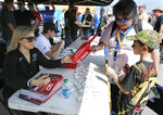 Natalie Decker, left, pole sitter for the ARCA auto race at Daytona International Speedway, signs autographs for fans, Saturday, Feb. 10, 2018, in Daytona Beach, Fla. (AP Photo/Terry Renna)