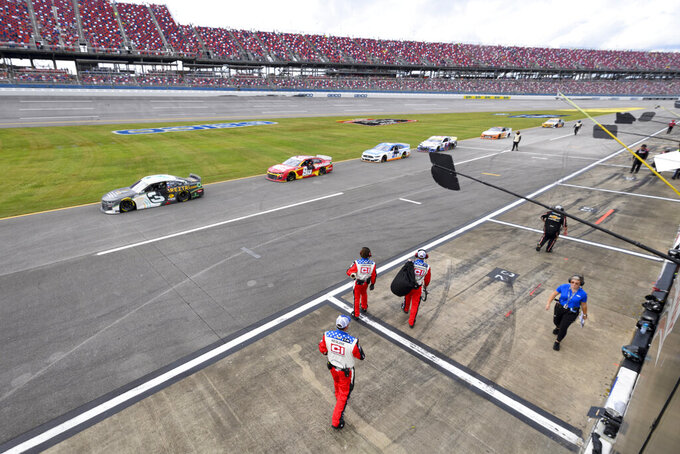 Cars are parked on pit row during a rain delay of a NASCAR Cup series auto race Monday, Oct. 4, 2021, in Talladega, Ala. (AP Photo/John Amis)