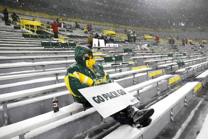 FILE - A few fans watch in Lambeau Field during the first half of an NFL football game between the Green Bay Packers and the Tennessee Titans in Green Bay, Wis., in this Sunday, Dec. 27, 2020, file photo. The eight teams hosting NFL playoff games this month are more than happy to be staying home with all of comfort it brings, but the actual advantage of playing there all but disappeared during this pandemic season of mostly empty stadiums. (AP Photo/Mike Roemer, File)