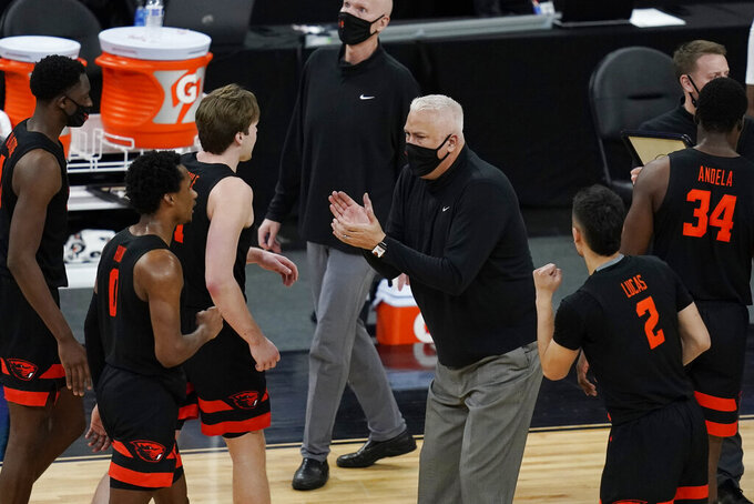 Oregon State head coach Wayne Tinkle claps for his players at a time out during the second half of an NCAA college basketball game against UCLA in the quarterfinal round of the Pac-12 men's tournament Thursday, March 11, 2021, in Las Vegas. (AP Photo/John Locher)