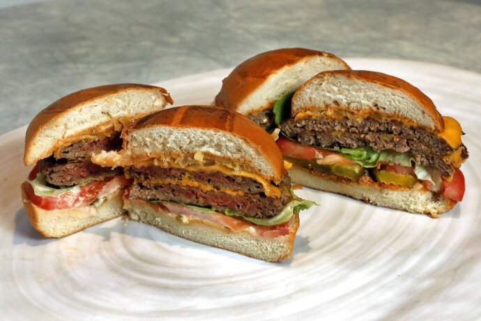 FILE - This Friday, May 3, 2019 file photo shows an Original Impossible Burger, left, and a Cali Burger, from Umami Burger, in New York. A new era of meat alternatives is here, with Beyond Meat becoming the first vegan meat company to go public and Impossible Burger popping up on menus around the country. Several new vegetarian products are competing to win over meat lovers, but two California companies _ Impossible Foods and Beyond Meat _ are grabbing attention for patties that are red before they're cooked, making them resemble raw beef. (AP Photo/Richard Drew)