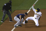 Oakland Athletics' Marcus Semien, right, is tagged out at third base by Seattle Mariners' Kyle Seager, center, during the third inning of a baseball game in Oakland, Calif., Friday, Sept. 25, 2020. (AP Photo/Jed Jacobsohn)