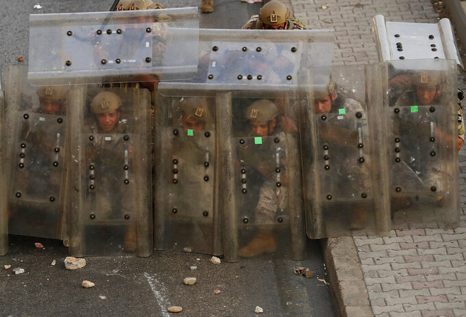 """Lebanese soldiers hide from stones behind their protective shields as they clash with supporters of Prime Minister-designate Saad Hariri who stepped down on Thursday in Beirut, Lebanon, Thursday, July 15, 2021. Hariri cited citing """"key differences"""" with the country's president, Michel Aoun, when he made the announcement, nine months after he was named to the post by the parliament. (AP Photo/Hussein Malla)"""
