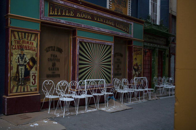 Painted white chairs stand outside a closed coffee shop, in Psiri district of Athens, on Tuesday, March 9, 2021.Greek authorities have announced a new record high in daily COVID-19 infections for this year, and one of the highest figures since the beginning of the pandemic. (AP Photo/Petros Giannakouris)