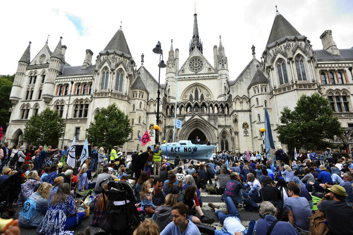Protesters from from the environmental pressure group Extinction Rebellion demonstrate outside the Royal Courts of Justice in London, Monday July 15, 2019.  Environmental campaigners are blocking some roads across the UK on Monday, as they protest against what they allege is