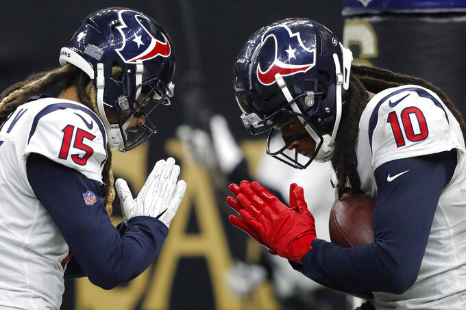 Houston Texans wide receiver DeAndre Hopkins (10) celebrates his second touchdown reception with wide receiver Will Fuller (15) in the second half of an NFL football game against the New Orleans Saints in New Orleans, Monday, Sept. 9, 2019. (AP Photo/Bill Feig)