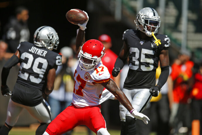 Kansas City Chiefs wide receiver Mecole Hardman (17) celebrates after scoring a touchdown during the first half of an NFL football game against the Oakland Raiders Sunday, Sept. 15, 2019, in Oakland, Calif. At left is Oakland Raiders free safety Lamarcus Joyner (29) and free safety Curtis Riley (35). (AP Photo/D. Ross Cameron)