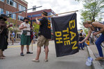 Abby McGinty straightens out Jojo Vinay's flag protesting the designated hitter rule shortly before the Pittsburgh Pirates take on the Chicago Cubs in the Pirates home opening baseball game at PNC Park in Pittsburgh, Thursday, April 8, 2021. (Steven Mellon/Pittsburgh Post-Gazette via AP)