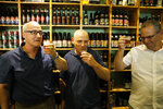 Prof. Aren Maeir, from Bar Ilan University, left, raises a toast with Dr Yitzchak Paz, from the Israeli Antiquities Authority, center, and Prof. Yuval Gadot, from Tel Aviv University during a press conference in Jerusalem, Wednesday, May 22, 2019. Israeli researchers raised a glass Wednesday to celebrate a long-brewing project of making beer and mead using yeasts extracted from ancient clay vessels -- some over 5,000 years old. Archaeologists and microbiologists teamed up to study yeast colonies found in microscopic pores in ancient pottery fragments. (AP Photo/Sebastian Scheiner)