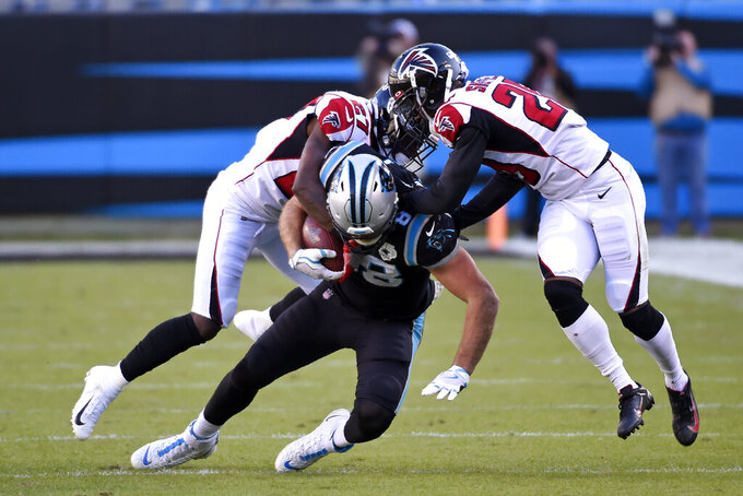 Atlanta Falcons defensive back Kendall Sheffield, right, and strong safety Damontae Kazee (27) tackle Carolina Panthers tight end Greg Olsen (88) during the second half of an NFL football game in Charlotte, N.C., Sunday, Nov. 17, 2019. (AP Photo/Mike McCarn)