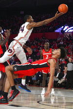 Auburn forward Anfernee McLemore (24) releases a shot as Georgia forward Toumani Camara tries to draw a charge during the first half of an NCAA college basketball game Wednesday, Feb. 19, 2020, in Athens, Ga. (AP Photo/John Amis)