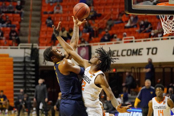 West Virginia forward Derek Culver (1) shoots over Oklahoma State forward Kalib Boone (22) in the first half of an NCAA college basketball game Monday, Jan. 4, 2021, in Stillwater, Okla. (AP Photo/Sue Ogrocki)