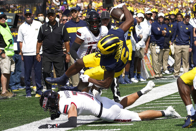 Michigan wide receiver Cornelius Johnson (6) is upended by Northern Illinois safety Jordan Hansen (7) during the first half of an NCAA college football game in Ann Arbor, Mich., Saturday, Sept. 18, 2021. (AP Photo/Paul Sancya)