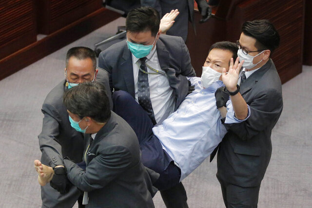 FILE - In this May 8, 2020, file photo, then pan-democratic legislator Ray Chan is taken away by security guards during a Legislative Council's House Committee meeting in Hong Kong. Hong Kong police arrested three former opposition lawmakers, Chan, Ted Hui and Eddie Chu, Wednesday, Nov. 18, 2020 for disrupting legislative meetings several months ago, as concerns grow over a crackdown on the city's pro-democracy camp. (AP Photo/Kin Cheung, File)