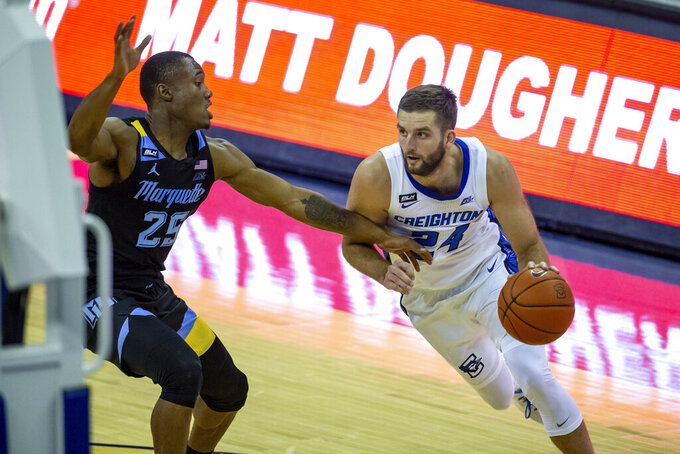 Creighton guard Mitch Ballock (24) drives to the basket against Marquette guard Koby McEwen (25) in the second half during an NCAA basketball game on Monday, Dec. 14, 2020, in Omaha, Neb. (AP Photo/John Peterson)