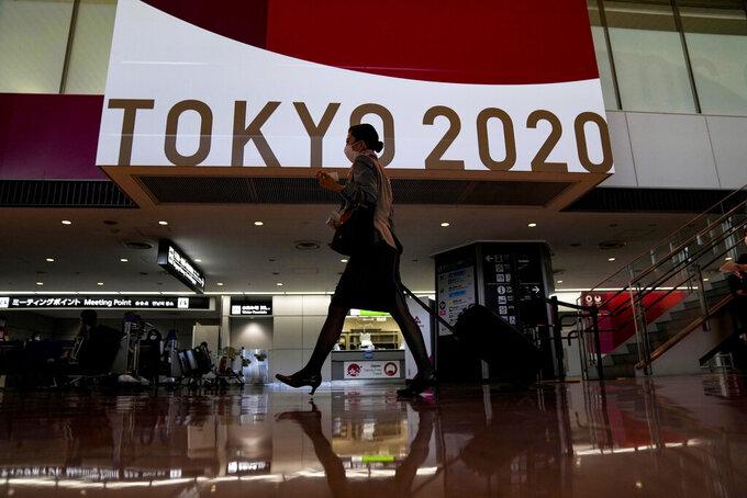 FILE - In this July 15, 2021, file photo, a flight attendant walks by a large display of Tokyo 2020 Olympics at Narita International Airport in Narita, east of Tokyo. (AP Photo/Kiichiro Sato, File)
