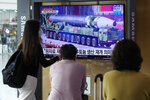 """People watch a TV screen showing a file image of a North Korean missile in a military parade during a news program at the Seoul Railway Station in Seoul, South Korea, Monday, Aug. 30, 2021. North Korea appears to have restarted the operation of its main nuclear reactor used to produce weapons fuels, the U.N. atomic agency said, as the North openly threatens to enlarge its nuclear arsenal amid long-dormant nuclear diplomacy with the United States. Korean letters read: """"The reactor produces plutonium."""" (AP Photo/Ahn Young-joon)"""