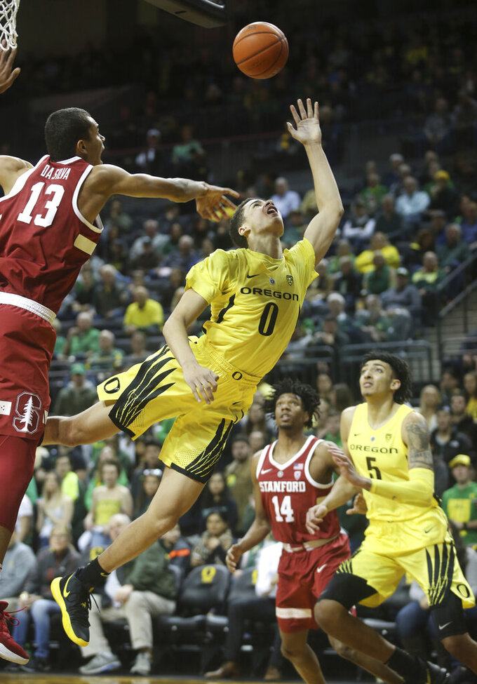 Stanford's Oscar da Silva, left, blocks a shot by Oregon's Will Richardson, center, as Stanford's Marcus Sheffield and Oregon's Miles Norris move in during the first half of an NCAA college basketball game Sunday, Feb. 10, 2019, in Eugene, Ore. (AP Photo/Chris Pietsch)