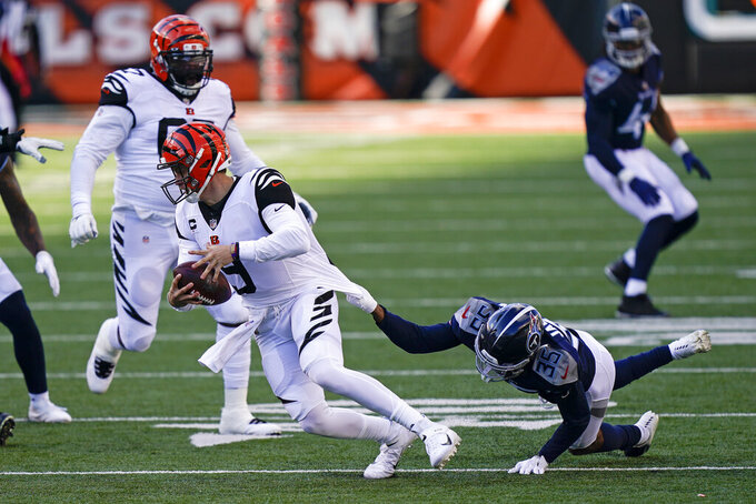 Cincinnati Bengals quarterback Joe Burrow (9) runs against Tennessee Titans' Chris Jackson (35) during the second half of an NFL football game, Sunday, Nov. 1, 2020, in Cincinnati. (AP Photo/Bryan Woolston)