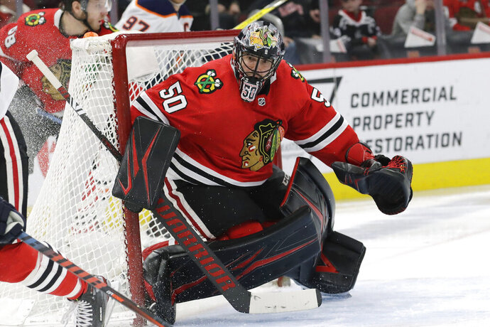 "FILE  - In this March 5, 2020, file photo, Chicago Blackhawks goalie Corey Crawford watches the puck during the second period of an NHL hockey game against Edmonton in Chicago. The Chicago Blackhawks will not re-sign goaltender Corey Crawford in free agency, potentially signaling a more extensive rebuild for one of the NHL's marquee franchises. General manager Stan Bowman said he had a ""bit of an emotional"" conversation with Crawford on Thursday, Oct. 8, 2020. (AP Photo/Nam Y. Huh, File)"