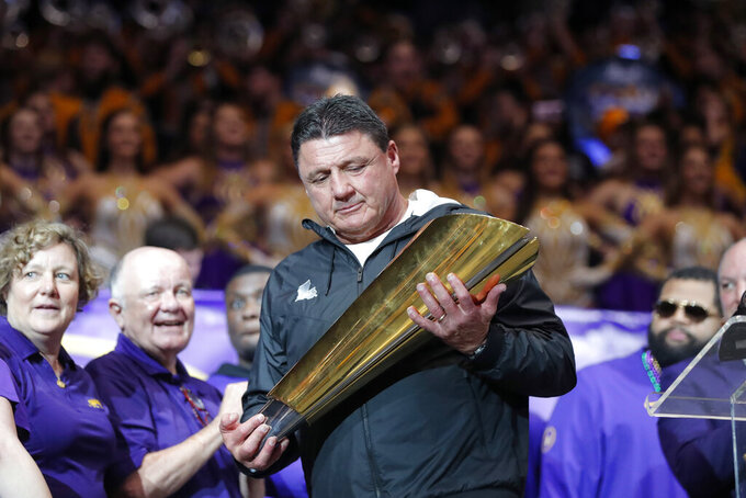 LSU head coach Ed Orgeron holds the national championship trophy during a celebration of the team's NCAA college football championship, Saturday, Jan. 18, 2020, on the LSU campus in Baton Rouge, La. (AP Photo/Gerald Herbert)