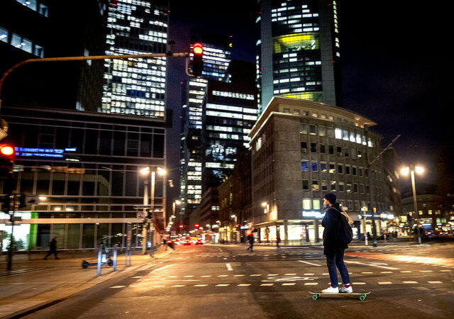 A young man wears a face mask as he crosses a road on his skateboard in downtown Frankfurt, Germany, Thursday, Nov. 26, 2020. The German parliament discussed the new restrictions to avoid the outspread of the coronavirus today. (AP Photo/Michael Probst)