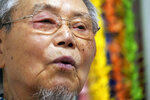 Lee Jong-keun speaks his experience of atomic bombing during an interview with The Associated Press in Hiroshima, western Japan, Tuesday, Aug. 4, 2020. Lee kept his secret as an atomic bombing survivor for nearly 70 years, not even telling his wife, always fearing people might notice the burn marks on the face. But today Lee, a second-generation Korean born in Japan, is training young people to tell survivors' stories. He also wants them to learn about the difficulty that Koreans have faced in Japan. (AP Photo/Eugene Hoshiko)