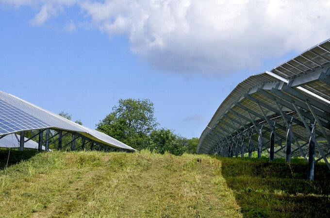 This June 15, 2021 photo shows a view of the Sugar Hill Solar Site in Clifton Park, N.Y.  The site is owned by Standard Solar Inc., and Developed by US Light Energy of Latham, N.Y.  Solar farms, wind turbines and hydro dams are producing more renewable power for the state, but it can be difficult to deliver that power south to the massive New York City market.   (AP Photo/Hans Pennink)