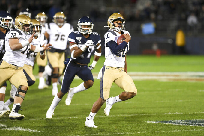 Navy quarterback Malcolm Perry (10) takes the ball in for Navy's first touchdown during the first half of an NCAA college football game against Connecticut on Friday, Nov. 1, 2019, in East Hartford, Conn. (AP Photo/Stephen Dunn)