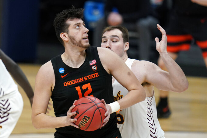 Oregon State center Roman Silva (12) drives past Loyola Chicago center Cameron Krutwig during the second half of a Sweet 16 game in the NCAA men's college basketball tournament at Bankers Life Fieldhouse, Saturday, March 27, 2021, in Indianapolis. (AP Photo/Jeff Roberson)