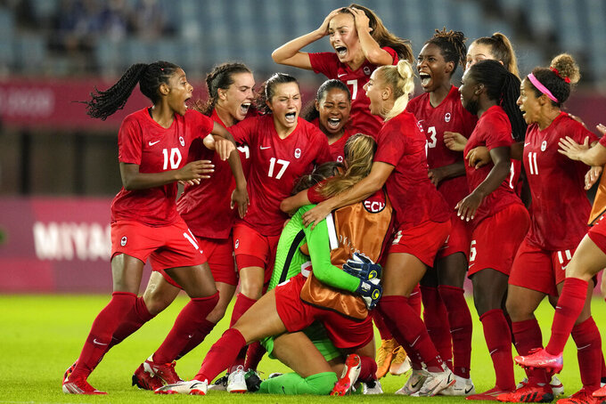 Canada's players celebrate winning 4-3 in a penalty shootout against Brazil during a women's quarterfinal soccer match at the 2020 Summer Olympics, Friday, July 30, 2021, in Rifu, Japan. (AP Photo/Andre Penner)