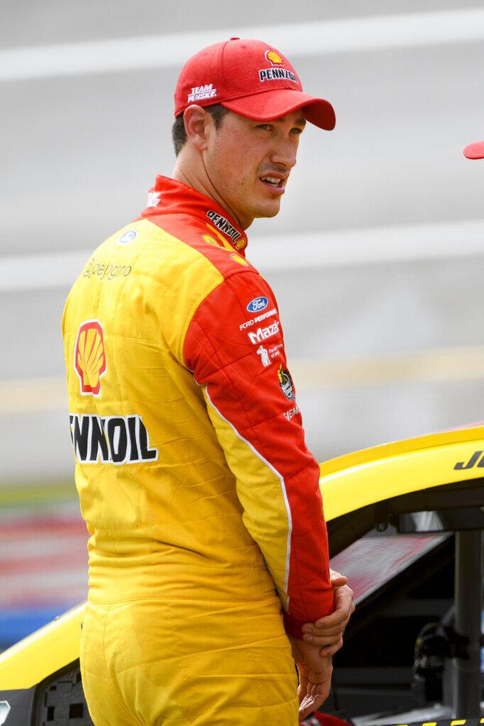 Joey Logano waits at his car during a rain delay in a NASCAR Cup series auto race Monday, Oct. 4, 2021, in Talladega, Ala. (AP Photo/John Amis)